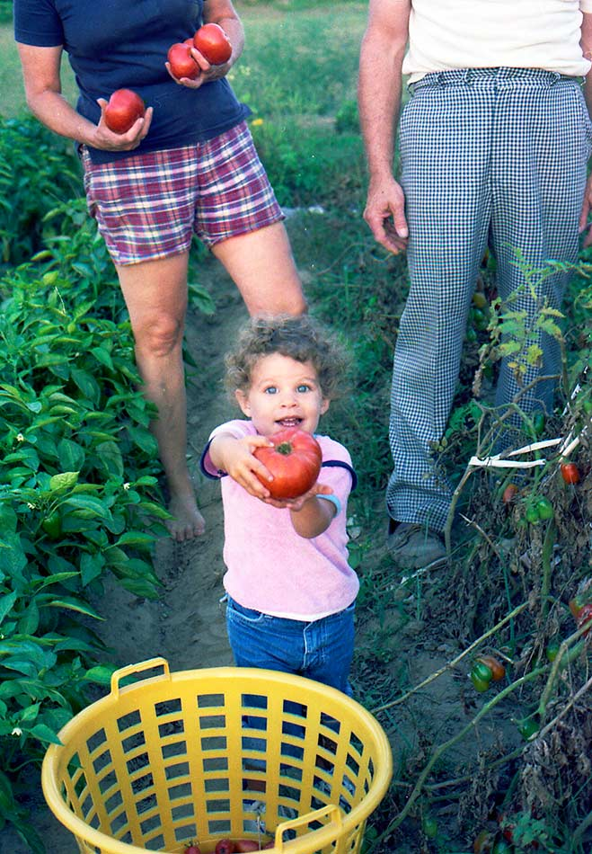 Kristin's prize tomato. Her grandparents are behind her with their heads cut off (?!!)